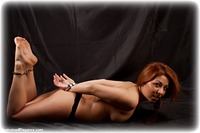 Free bondage photo Aisha barefoot, handcuffs, leg irons, lingerie, metal bondage, topless, ungagged