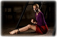 Free bondage photo Ariel Anderssen barefoot, blonde, shackles, skirt, leg irons, chains, collar, sweater, tape gag, ungagged