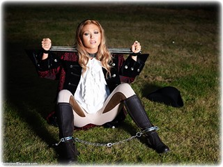 Bondage photo pic picture Natalia Forrest historical, blouse, boots, jodhpurs, brunette, leg irons, metal bondage, outdoor, ungagged, yoke
