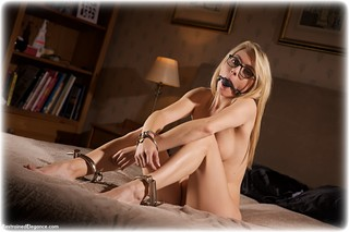 Bondage photo pic picture Chloe T ballgag, glasses, barefoot, globe cuffs, bedroom, handcuffs, blonde, leg irons, metal bondage, nude