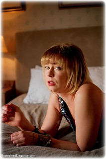 Bondage photo pic picture Lucy Lauren barefoot, bedroom, handcuffs, blonde, leg irons, metal bondage, dress, ungagged