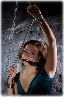 Bondage photo pic picture Alicia ballgown, barefoot, shackles, brunette, sm factory, leg irons, chains, spreader bar, cloth gag, metal bondage, dungeon, ungagged, velvet