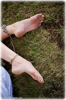 Bondage photo pic picture Ariel Anderssen barefoot, handcuffs, blonde, blouse, skirt, leg irons, metal bondage, outdoor, topless, ungagged