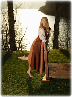 Bondage photo pic picture Ariel Anderssen barefoot, gown, handcuffs, blonde, historical, humiliation, medieval, metal bondage, stocks, outdoor, ungagged