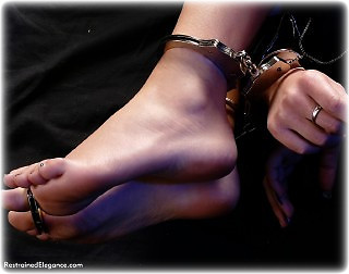 Bondage photo pic picture Belle barefoot, handcuffs, bit gag, leg irons, metal bondage, uniform