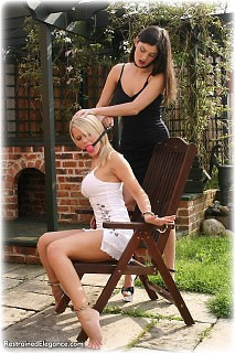 Bondage photo pic picture Angelina and Jasmine Sinclair ballgag, girlgirl, barefoot, handcuffs, humiliation, leg irons, lesbian, metal bondage, outdoor