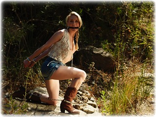Bondage photo pic picture Katy Cee bit gag, handcuffs, boots, humiliation, jeans, leg irons, lingerie, metal bondage, nude, outdoor, topless, ungagged