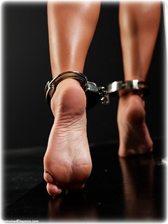 Bondage photo pic picture Natalia Forrest barefoot, handcuffs, blouse, shoes, business wear, skirt, leg irons, lingerie, metal bondage, nude, ungagged